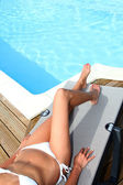 Closeup on legs of woman relaxing in deck chair by pool — Stock Photo