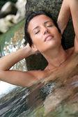 Glamorous woman showering in natural springs — Stock Photo