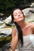 Beautiful young woman applying hair conditioner sitting by river — Stock Photo