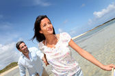 Cheerful couple walking by the sea — Stock Photo