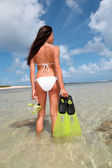 Back view of woman holding snorkeling accessories by the sea — Stock Photo
