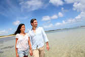 Cheerful couple walking by the sea — Stockfoto