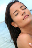Portrait of woman enjoying the sun at the beach — Stock Photo