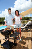 Young couple cooking dinner on barbecue grill — Stock Photo