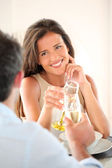 Woman cheering with glass of champaign in fancy restaurant — Stock Photo