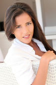 Portrait of attractive woman sitting in sofa at home — Foto de Stock