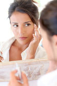 Portrait of beautiful woman applying anti-wrinkles cream — Stok fotoğraf