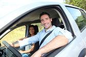 Happy couple riding car on vacation — Stock Photo