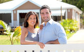 Couple standing in front of new home — Stock Photo