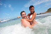 Cheerful couple enjoying the waves — Stock Photo
