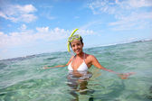 Smiling woman in water with snorkeling outfit — Stock Photo