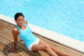 Brunette girl in fitness outfit relaxing by the pool — Stock Photo