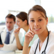 Portrait of beautiful nurse sitting in office, in background — Stock Photo