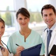 Stock Photo: Smiling medical team standing in hall