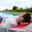 Mrelaxing in long chair by pool — Stock Photo #13960953