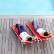 Couple relaxing in long chairs by outdoor pool — Stock Photo #13961075