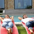 Couple relaxing in long chairs by outdoor pool — Stock Photo #13961077