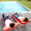 Couple relaxing in long chairs by outdoor pool — Stock Photo