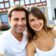 Cheerful couple sitting in front of new house — Foto de Stock