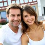 陽気なカップルの新しい家の前に座っています。 — Stock fotografie