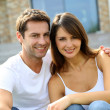 Cheerful couple sitting in front of new house — Stock Photo #13961094