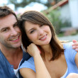 Cheerful couple sitting in front of new house — Stock Photo #13961113