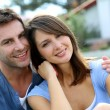 Royalty-Free Stock Photo: Cheerful couple sitting in front of new house
