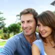 Cheerful couple sitting in front of new house — Stock Photo #13961114