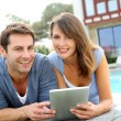 Couple websurfing on internet with tablet — ストック写真