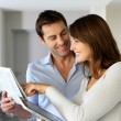 Couple at home reading news on newspaper and internet — Stock Photo
