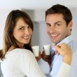 Cheerful couple holding cups of coffee — Stock Photo
