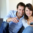 Couple sitting in couch choosing tv program — 图库照片