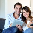 Couple sitting in couch choosing tv program - Stock Photo