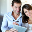 Mature couple at home using credit card to shop online — Stock Photo