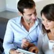 Mature couple at home using credit card to shop online -  