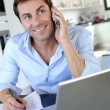 Home office worker talking on mobile phone — Stock Photo