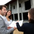 Couple meeting saleswoman on construction site — Stock Photo