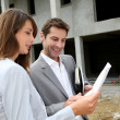 Couple on construction site checking building progress — Stock Photo #13961767