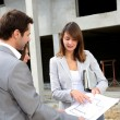 Couple meeting saleswoman on construction site — Stock Photo #13961788