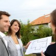 Couple meeting saleswoman on construction site - Stock Photo