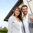 Couple in front of new home holding door keys — Stok fotoğraf