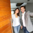 Couple opening the front door of their home - Stock Photo