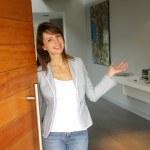 Woman opening her house door to welcome — Stock Photo