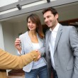 Stock Photo: New property owners shaking hands to sales agent
