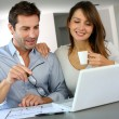 Couple at home looking at future home blueprint - Foto Stock