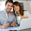 Couple at home looking at future home blueprint — Stock Photo #13962015