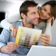 Couple choosing paint colour for their new home - Stock Photo