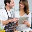 Couple in home kitchen using electronic tablet — Stock Photo #13962073