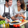 Couple in home kitchen using electronic tablet — Stock Photo #13962077