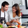 Couple in home kitchen using electronic tablet — Stockfoto